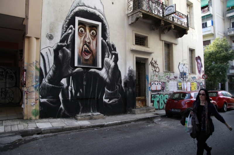 "Athens, Exarcheia: Α woman walks past the work ""capture""by Indonesian-born street artist WD (Wild Drawing). Photo: Dimitri Messinis, Associated Press-Ap (Source: www.startribune.com, 26.3.2014)"